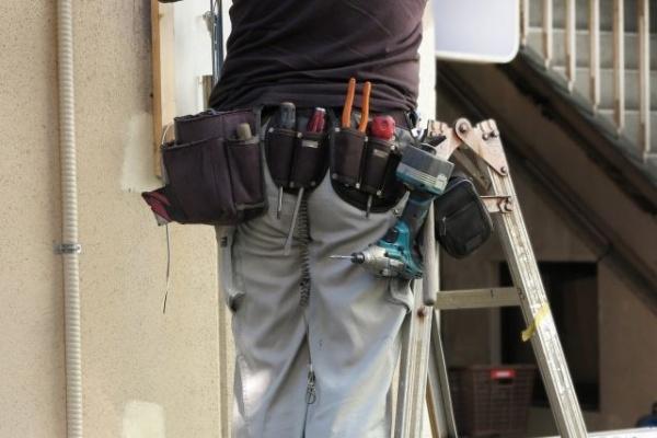 梯子に登って作業をしている業者